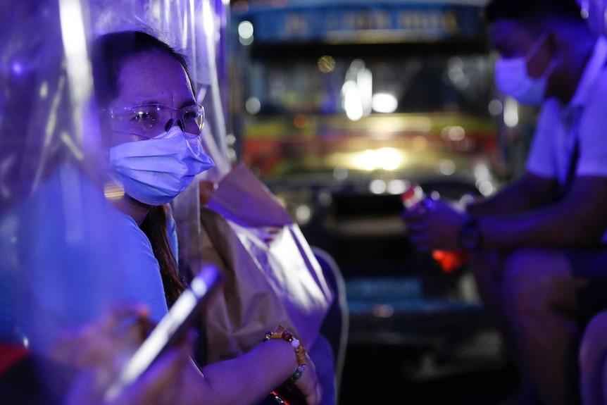 Una anciana con mascarilla y gafas se sienta en la noche con un autobús y un hombre enmascarado detrás de ella.