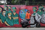 A motorists stops near a mural painted as a tribute to medical workers in Indonesia.