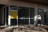 A photo of a vacant shopfront in Darwin's CBD as a man in businesswear walks past.