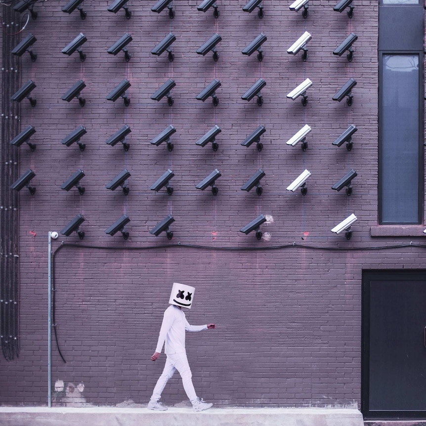 A person wearing all white and a mask with an emoji-style face walks past a wall with dozens of CCTV cameras on it.