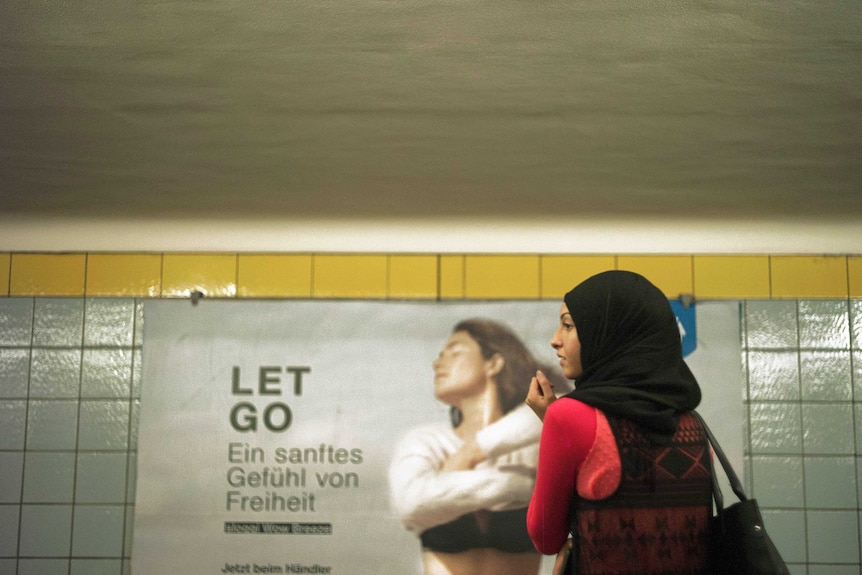 A woman in a hijjab stands in front of a German advertising board.