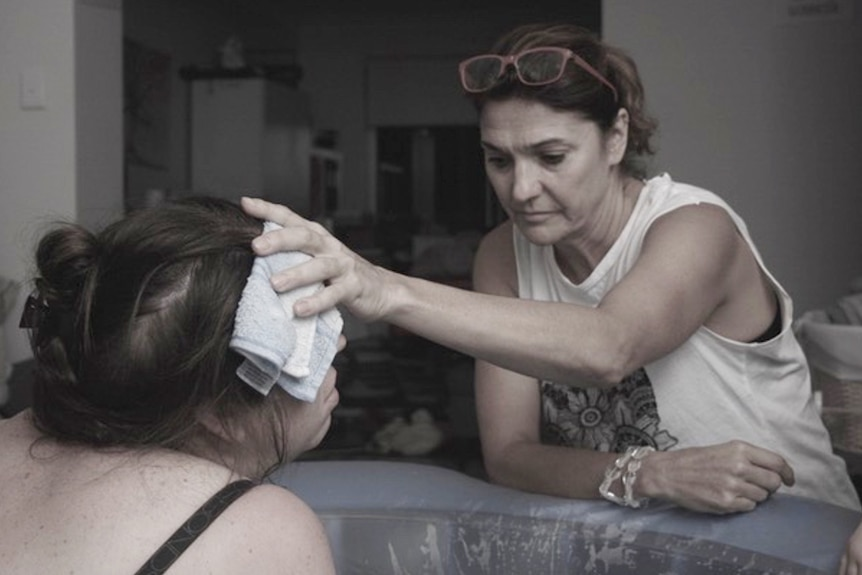 Renee Adair looking very still and focussed holds a wet flannel over the forehead of a woman in a birthing pool
