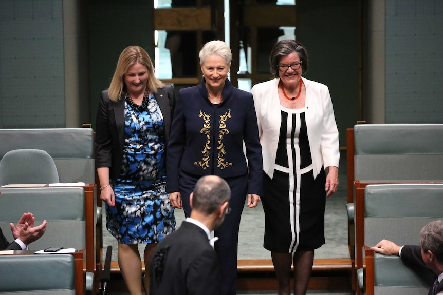 Three women smile as they walk into the House of Representatives
