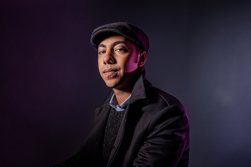 A man sits in front of grey backdrop with purple light on side of face in newsboy cap, shirt, jumper, coat with popped collar.