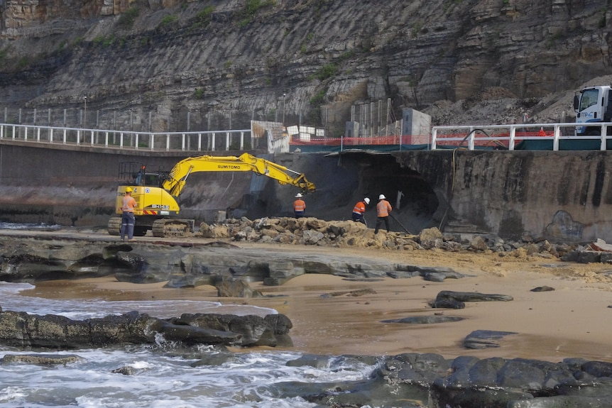 A large digging machine and a few workers surrounding a big hole in a sea wall.