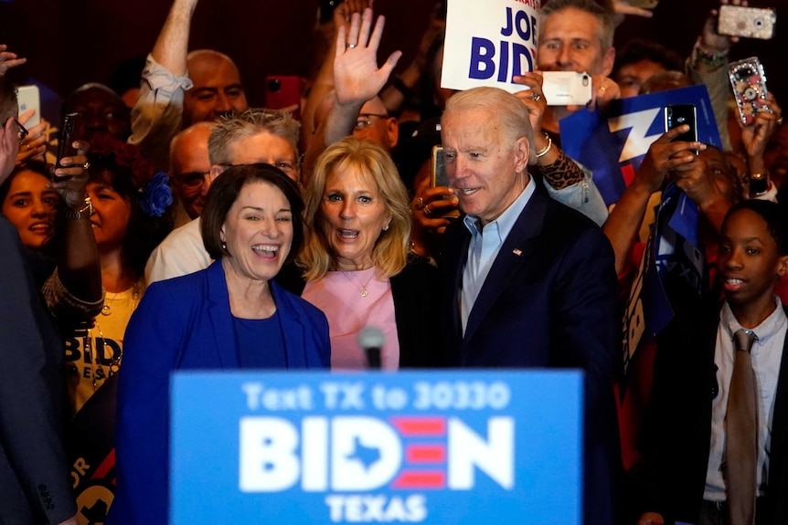 Joe Biden with his wife Jill and Amy Klobuchar surrounded by supporters