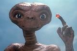 An alien holds up a lit finger