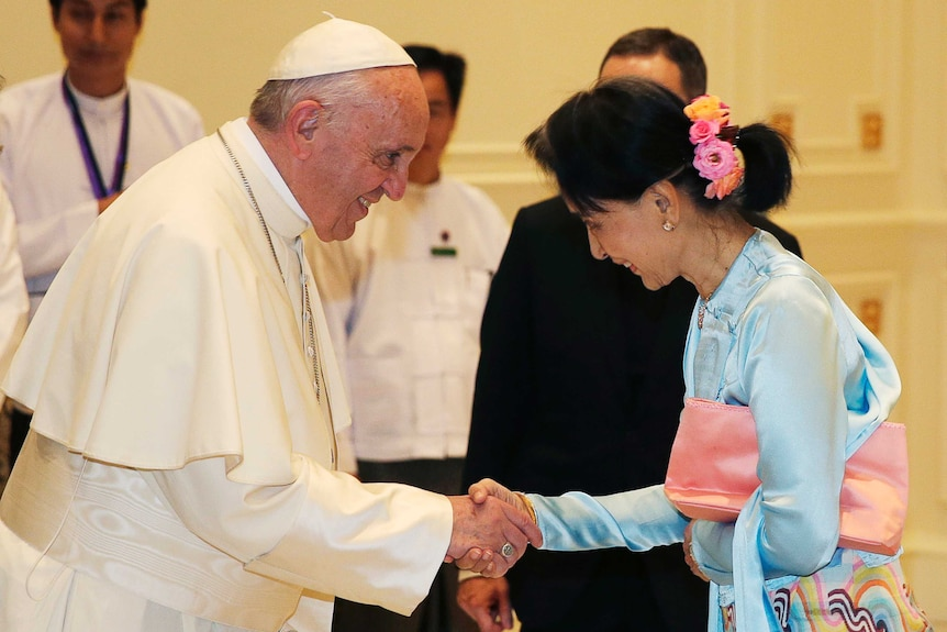 Pope Francis shakes hands with Aung San Suu Kyi.