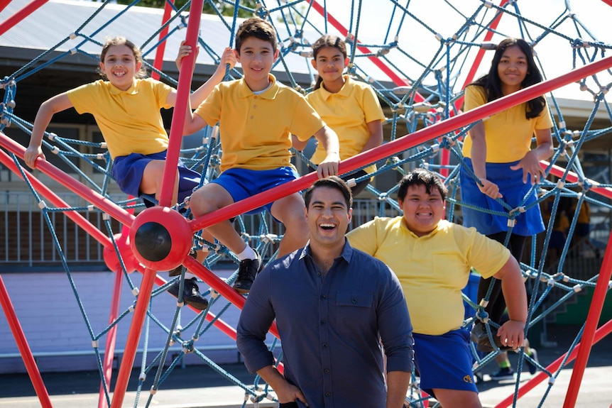 A man in a blue shirt poses for a photo with five primary school kids perched in a climbing apparatus