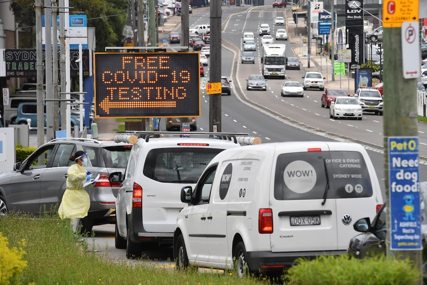 """Cars line up in front of an electronic sign that reads: """"Free COVID-19 testing""""."""