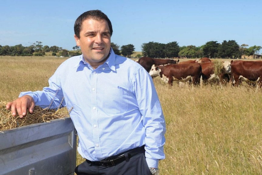 Tony Pasin leans against a ute tray filled with hay in a field with cows in the background.