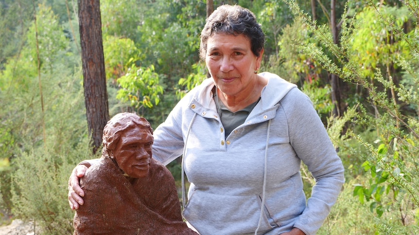 An Aboriginal woman with her arms around a statue of a woman.