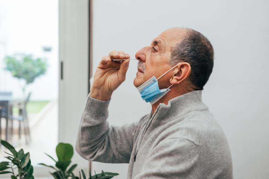 Man collects his own nasal swab.