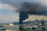 You view the charred cityscape of Beirut from its port as black smoke rises from the entrance to the port.