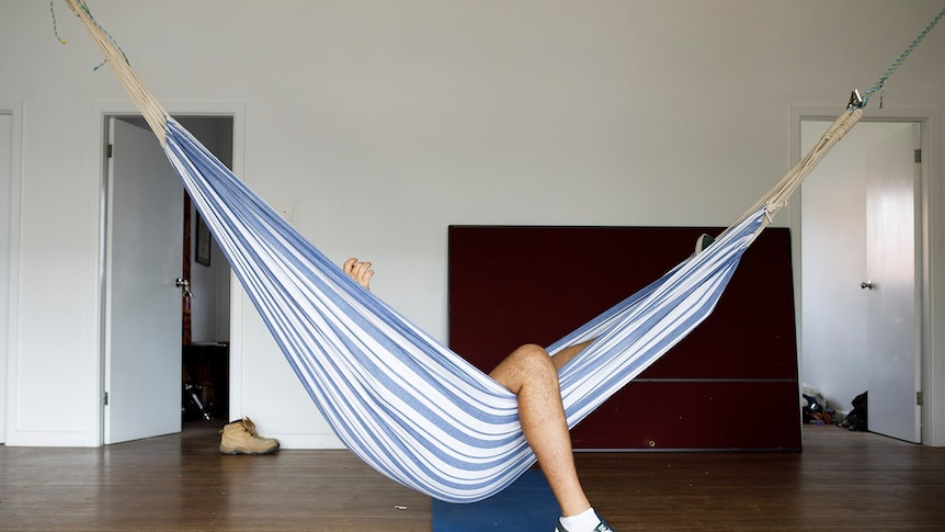 A hammock hangs in a large empty room with a person's leg visible out the side of it for a story on share housing.