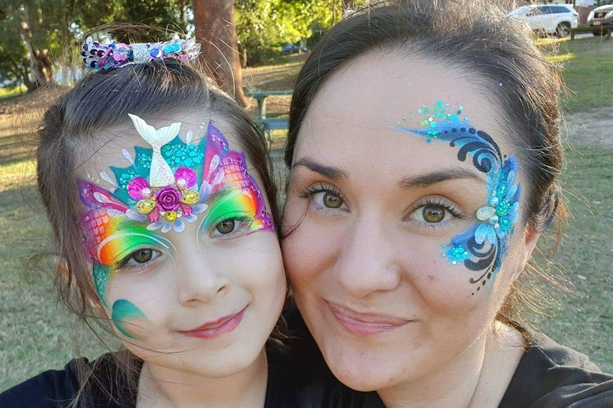 A young girl and her mother are smiling at the park, with colourful paint on their face.
