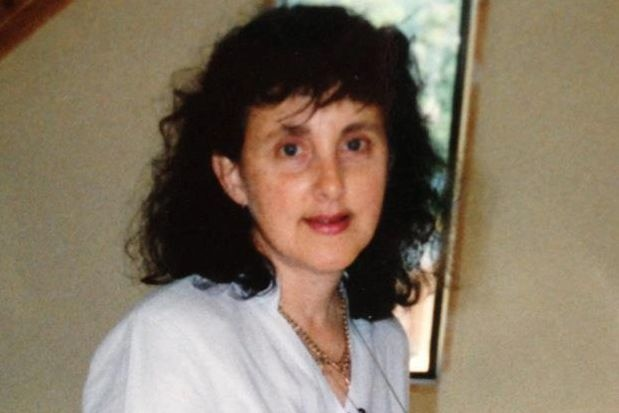 Medium close up of woman wearing white shirt looking into camera with a half-smile on her face.