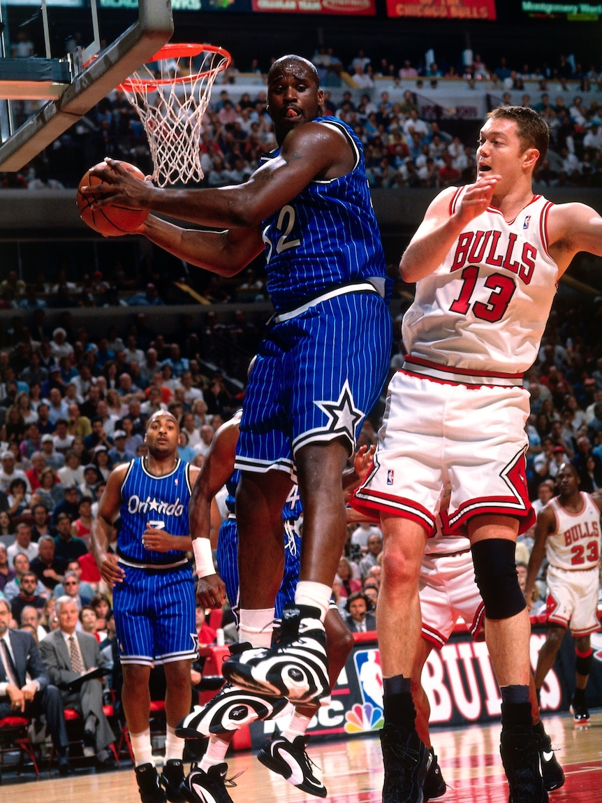 Luc Longley of the Chicago Bulls jumps in the air pushing on Shaquille O'Neal from Orlando Magic as they chase the ball