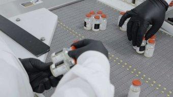 Inside a lab gloved hands are handling bottles of drugs