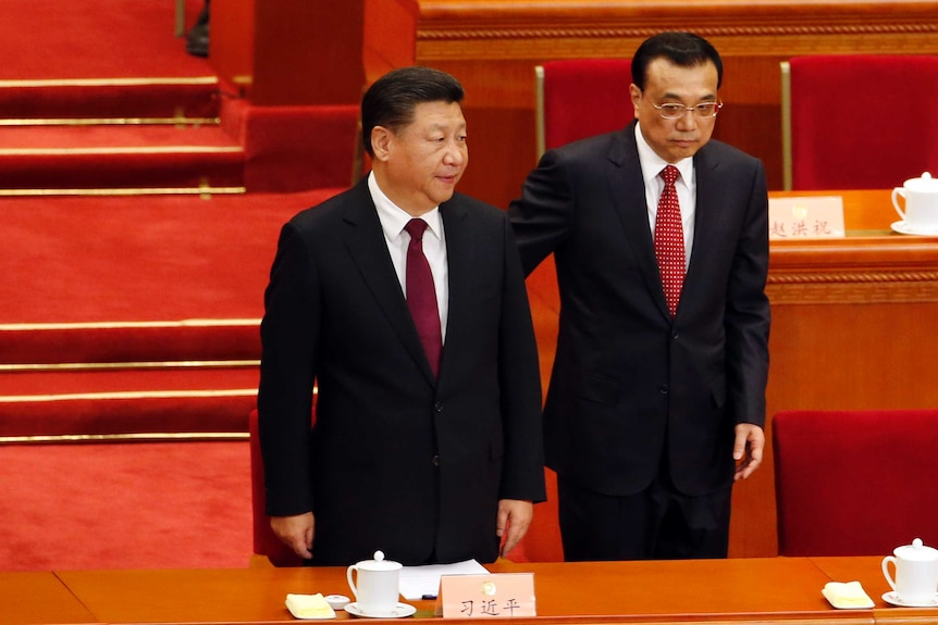 Chinese President and Premier stand before a table at meeting.
