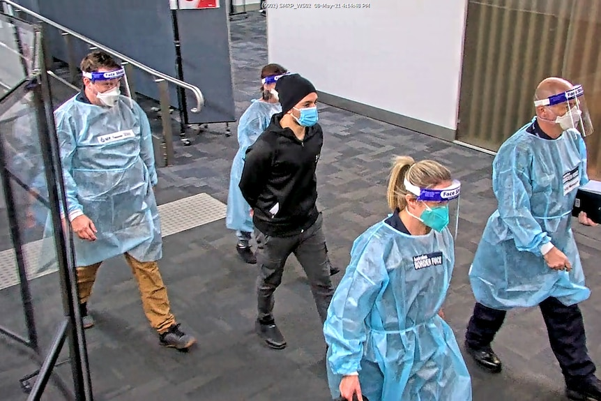 A young man in dark clothing and a surgical face mask, is escorted through an airport by four people in protective equipment.