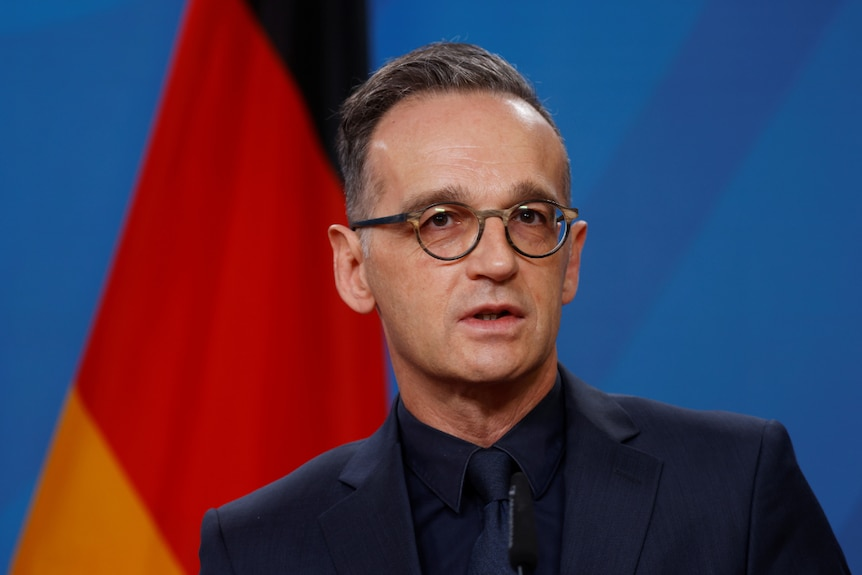You view Heiko Maas wearing a dark suit and shirt speaking in front of a blue background with a German flag behind him.