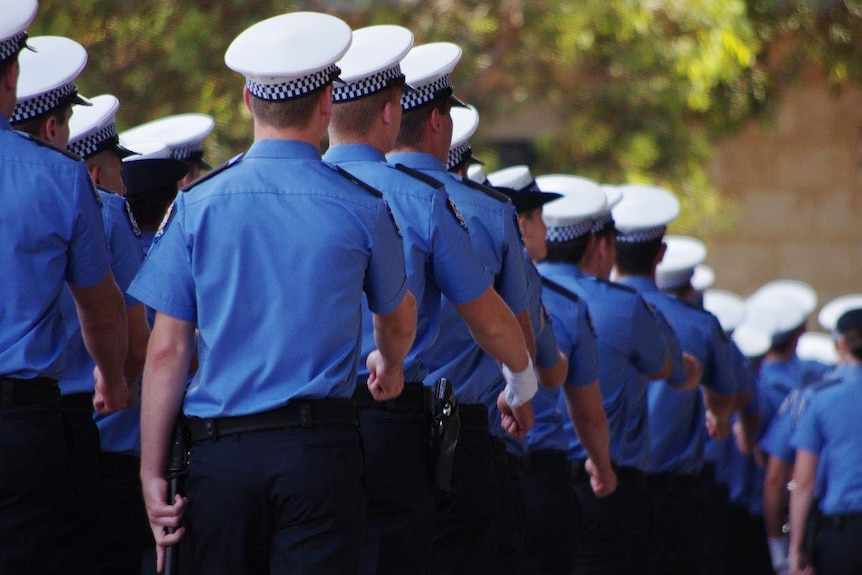 Police recruits march in uniform with their backs turned in a graduation ceremony.
