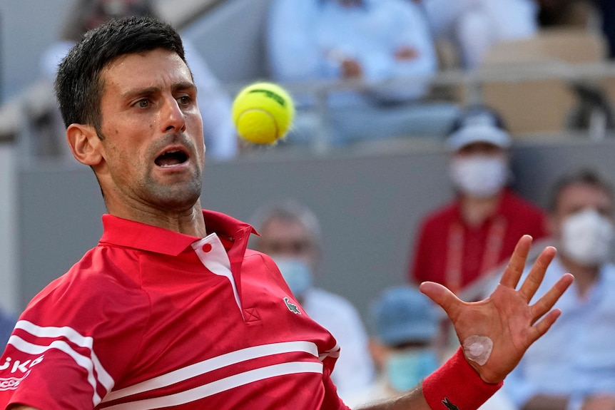 Novak Djokovic leans back and watches the ball