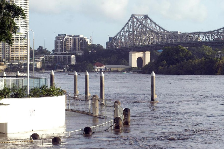 The submerged riverside walkway at a pier goes under in floods.