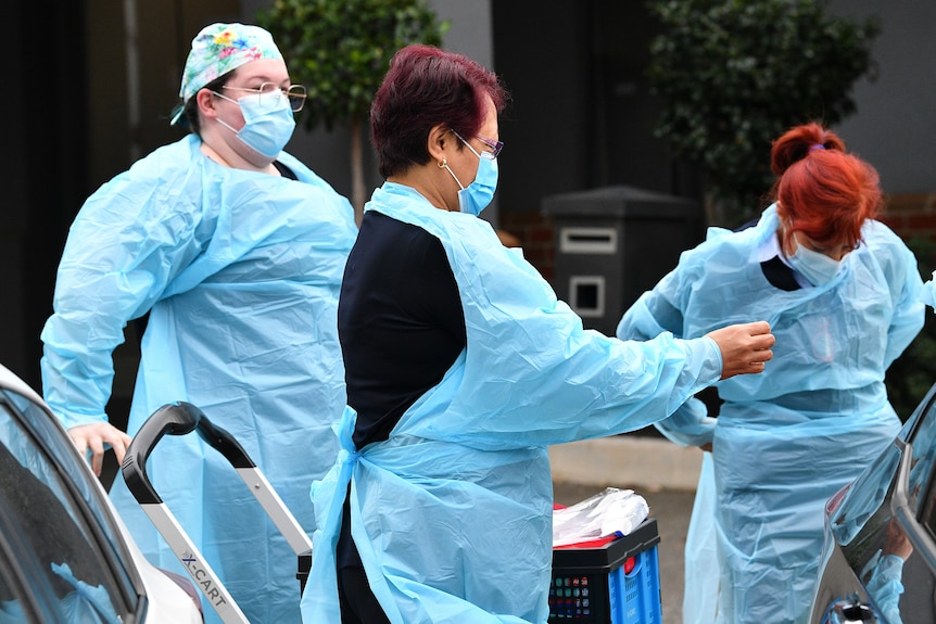 Three workers in blue PPE gowns prep to go inside an aged care home