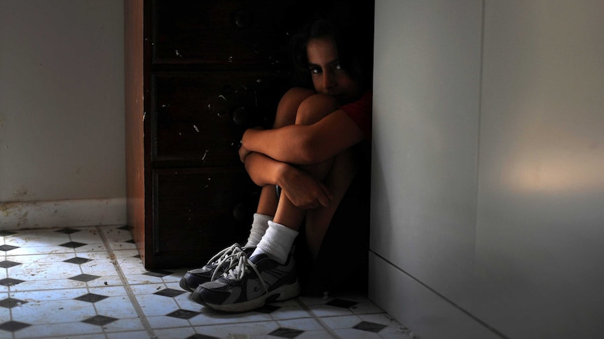 A child sits on the floor hunched in a corner next to a cupboard, peering over their knees.