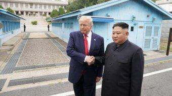 US President Donald Trump meets with North Korean leader Kim Jong-un shaking hands.