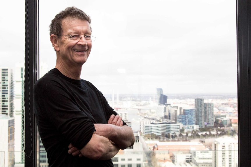Red Symons stands with his arms crossed, smiling, next to a window overlooking a city.