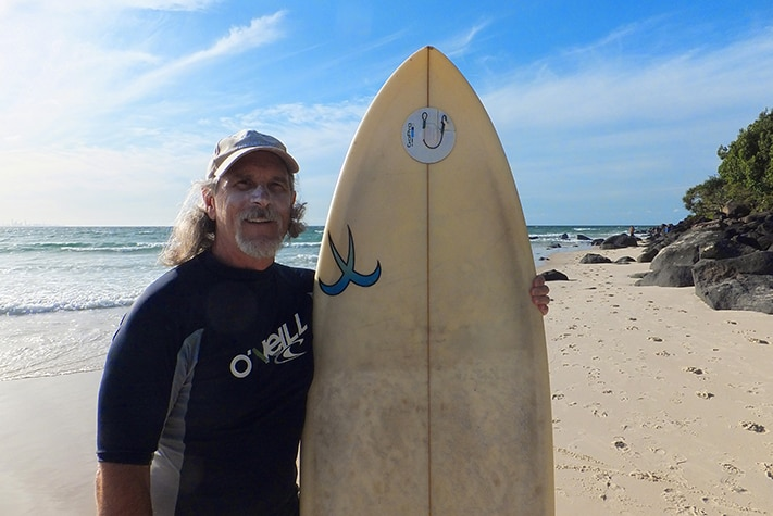 A middle-aged man with long grey hair and a goatee beard stands on the beach with his surfboard.
