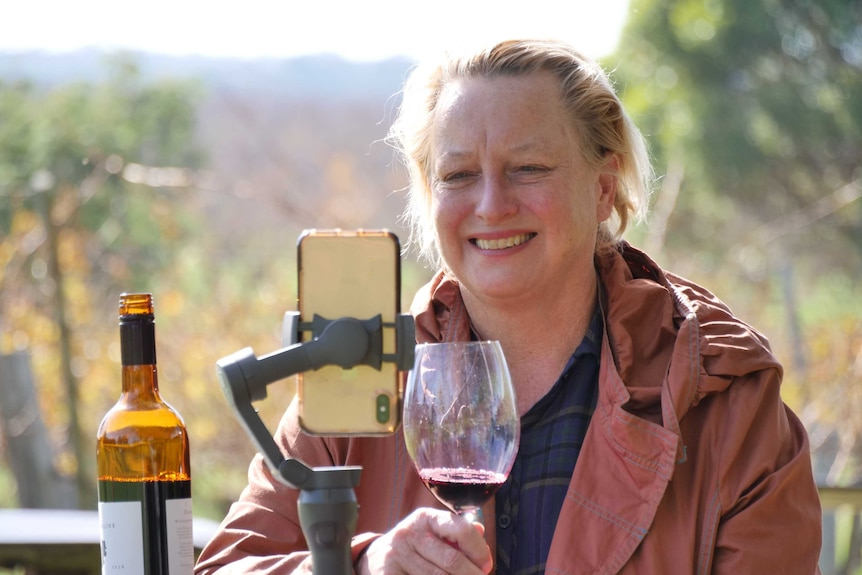 A woman with a glass of wine conducting virtual wine tastings.