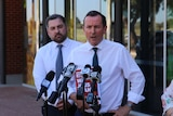 Mark McGowan holding a red election document with a man standing behind him, both standing at microphones.