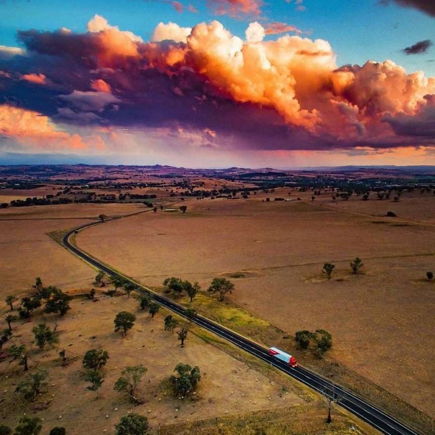 Aerial view of a semi-trailer driving along a rural highway with a township and setting sun in the distance.