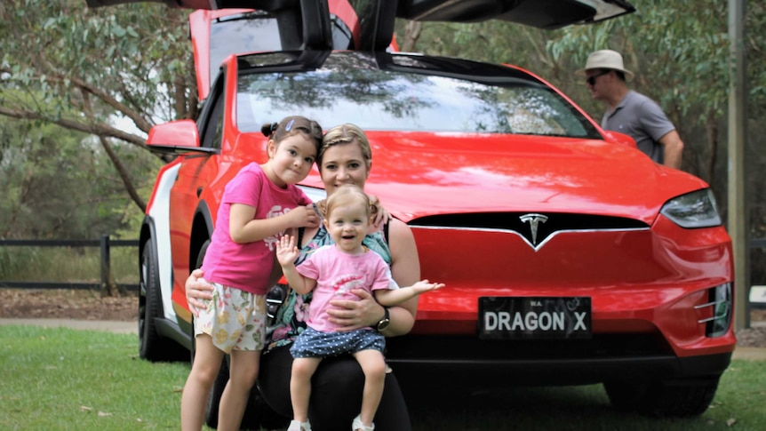 woman and two young children crouched in front of red car with sides open