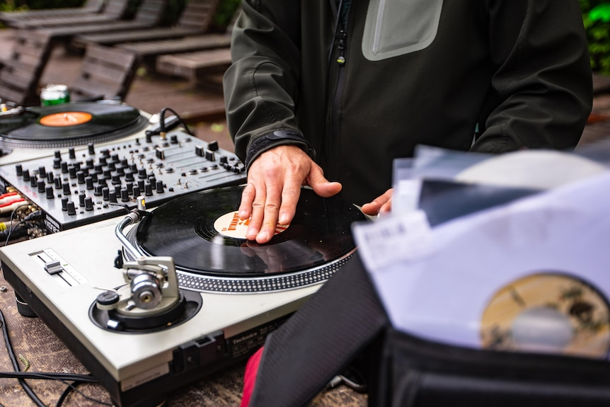 A DJ mixing songs using vinyl and turntables.