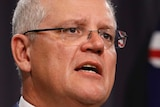 Scott Morrison stands in front of a blue curtain with an Australian flag behind him