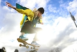 Australian skateboarder Hayley Wilson in the air on her board, wearing a beanie and a Tokyo Olympics kimono.