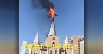 A still from a video shows a cross at the top of a church on fire.