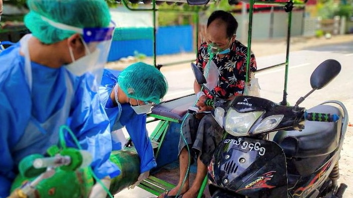 Two doctors in PPE assist with a oxygen tank for a man next to his motorcycle.