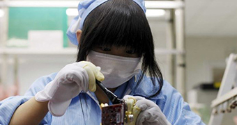 A woman wearing protective gear works with electronics in a lab environment.