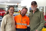 A man in a hi-vis vest stands between an older couple, his parents.