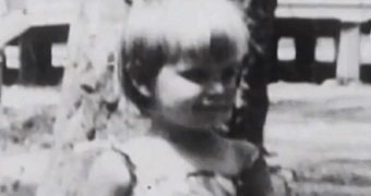 Black and white image of toddler with fair hair in front of tree