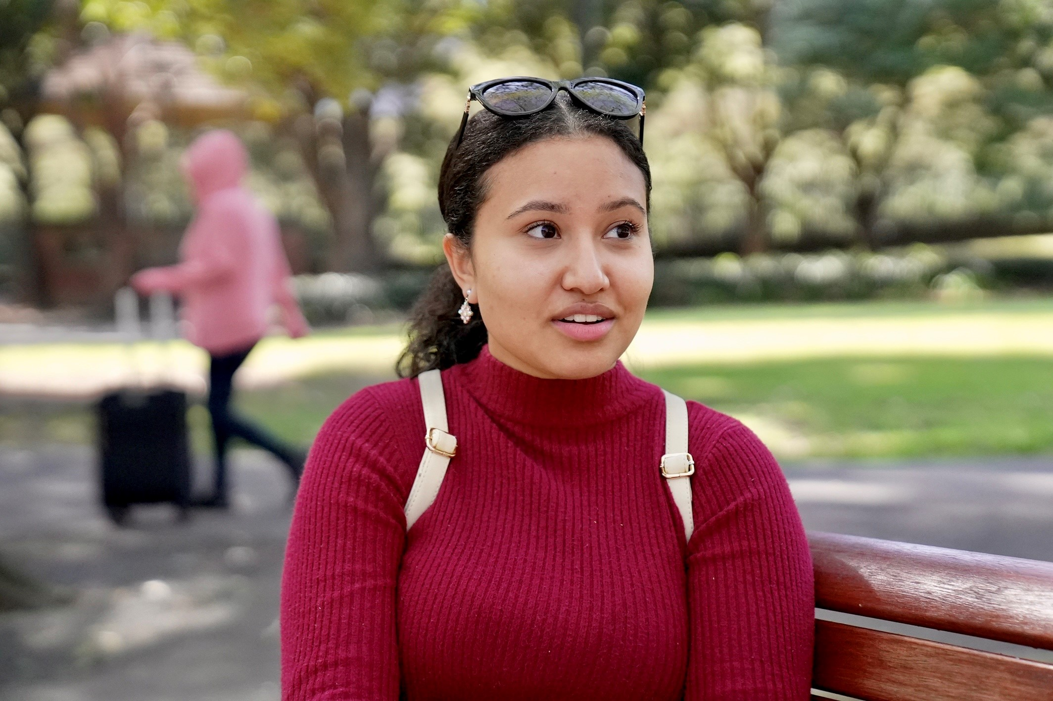 Steffy in a red jumper, sitting on a park bench looking perplexed.