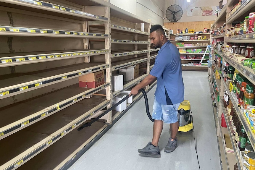 A man vacuums the empty shelves of a supermarket.
