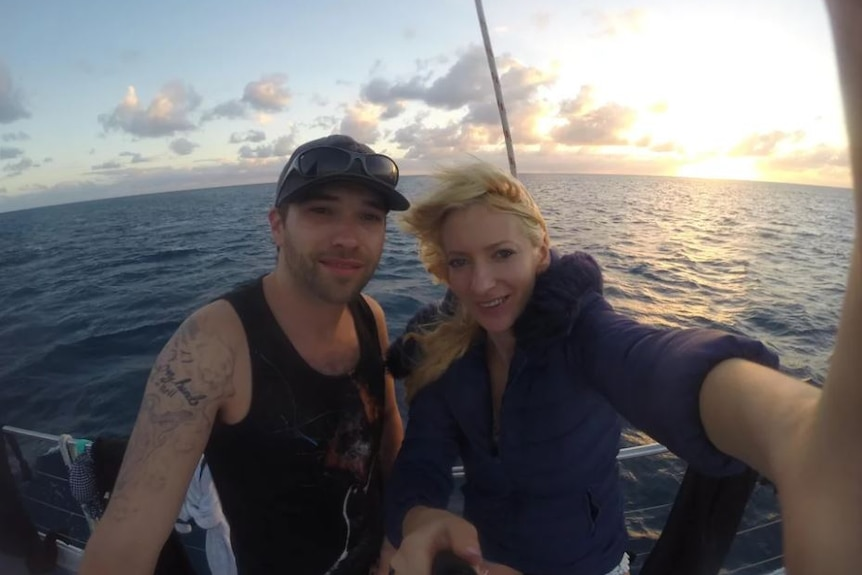 A man and woman smiles for a photo on a boat in the ocean