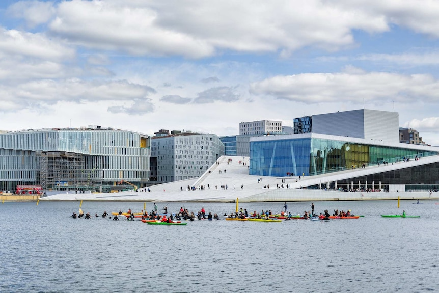 People on kayaks and paddleboards in the water in front of city buildings